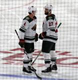 Mike Reilly and Kyle Quincey of the Minnesota Wild talk during a stop in play in a game against the Detroit Red Wings.