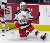 Dan Renouf of the Grand Rapids Griffins stretches near the boards during pre-game warmups before his team's season-opening game against the Manitoba Moose.