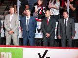 Grand Rapids Griffins coaches Mike Knuble, Bruce Ramsay, Ben Simon, and Todd Nelson stand behind the bench during player introductions at the start of their team's home opener against the Manitoba Moose.