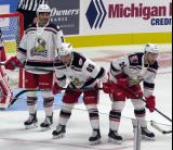 Robbie Russo, Dominik Shine, and Dylan Sadowy of the Grand Rapids Griffins get set for a faceoff during their team's home opener against the Manitoba Moose.