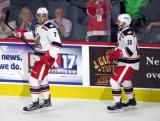 Ryan Sproul and Ben Street of the Grand Rapids Griffins skate along the boards after high-fiving teammates on the bench in celebration of a goal by Sproul during his team's home opener against the Manitoba Moose.