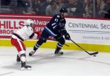 Robbie Russo of the Grand Rapids Griffins attempts to defend against Kyle Connor of the Manitoba Moose during the Griffins' home opener.