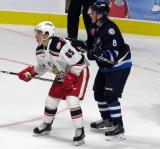 Sami Niku of the Manitoba Moose defends against Dominik Shine of the Grand Rapids Griffins during the Griffins' home opener.