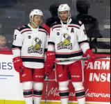 Robbie Russo and Brian Lashoff of the Grand Rapids Griffins stand at the boards during pre-game warmups before a game against the San Antonio Rampage.