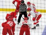 Joe Veleno, David Pope, and Otto Kivenmaki of the white team line up for a faceoff against Brady Gilmour and Luke Morgan of the red team during a scrimmage at the Detroit Red Wings' 2018 Development Camp.