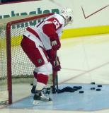 Kris Draper clears pucks out of the net and crease during pregame warmups.