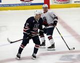 J.T. Compher of Team Blue and Alex Debrincat of Team White skate around each other at center ice during the 2018 Stars & Stripes Showdown.