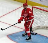 Luke Glendening clears pucks out of the net during pre-game warmups before the Red Wings' home opener against the Columbus Blue Jackets.