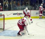 Chris Osgood reaches to make a stick save.  On his far side Pavel Datsyuk stickhandles and Steve Yzerman stands along the boards.