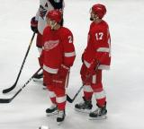 Joe Hicketts and Filip Hronek stand on the ice during a stop in the Red Wings' home opener against the Columbus Blue Jackets.