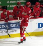 Dennis Cholowski gives the bench a round of high-fives after his first career NHL goal during the Red Wings' home opener against the Columbus Blue Jackets.