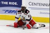 Givani Smith stretches near the boards during pre-game warmups before a game between the Grand Rapids Griffins and the Chicago Wolves.
