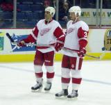 Chris Chelios and Johan Franzen watch their teammates during pregame warmups.