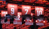 The banners for the first seven jersey numbers retired by the Red Wings in the Little Caesars Arena rafters, prior to Red Kelly's being raised to join them.