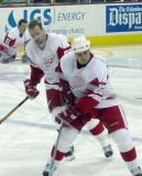 Tomas Holmstrom and Brett Lebda follow the puck while Dan Cleary stretches in the background.
