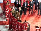 Red Kelly views the gifts given to him in honor of his jersey number retirement, with the current Red Wings team looking on.