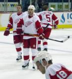 Dan Cleary and Mathieu Schneider watch pregame warmups while Nicklas Lidstrom skates in the background and Kirk Maltby skates in the foreground.