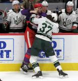 Dylan McIlrath of the Grand Rapids Griffins and Hunter Warner of the Iowa Wild fight in front of the Iowa bench during the Griffins' annual Purple Game.