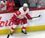 Andreas Athanasiou of the Detroit Red Wings crouches near the boards during pre-game warmups before a game against the Tampa Bay Lightning.