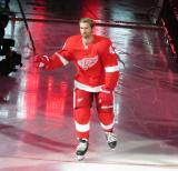 Darren Helm of the Detroit Red Wings raises his stick to the crowd during player introductions before the Red Wings' home opener against the Dallas Stars.
