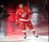 Luke Glendening of the Detroit Red Wings raises his stick to the crowd during player introductions before the Red Wings' home opener against the Dallas Stars.