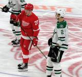 Adam Erne of the Detroit Red Wings and Jamie Oleksiak of the Dallas Stars skate during a stop in play.