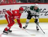 Anthony Mantha of the Detroit Red Wings and Miro Heiskanen of the Dallas Stars line up opposite each other on a faceoff.