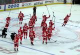 The Detroit Red Wings raise their sticks at center ice to salute their fans after a win over the Dallas Stars in Detroit's home opener.