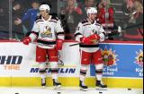 Gustav Lindstrom and Ryan Kuffner of the Grand Rapids Griffins stand at the boards during pre-game warmups before a game against the Milwaukee Admirals.