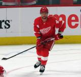 Luke Glendening of the Detroit Red Wings through a faceoff circle during pre-game warmups before a game between the Red Wings and the Calgary Flames.