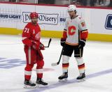 Dylan Larkin of the Detroit Red Wings and Noah Hanifin of the Calgary Flames stand at the blue line during a stop in play in a game between the Red Wings and Flames.