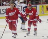 Kris Draper and Henrik Zetterberg watch their teammates during pregame warmups, with Brian Campbell skating behind them.
