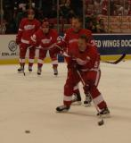 Nicklas Lidstrom starts to take a shot on goal during pregame warmups while Valtteri Filppula, Henrik Zetterberg and a Kris Draper look on.