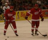 Valtteri Filppula and Henrik Zetterberg stickhandle at center ice during pregame warmups.