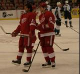Robert Lang and Jiri Hudler stand inside the blue line during pregame warmups.
