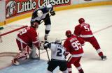 Dominik Hasek guards the near post as Nicklas Lidstrom poke-check's LA's Derek Armstrong at the side of the net.  Danny Markov guards Alexander Frolov at the top of the crease.