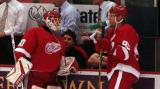 Chris Osgood and Danny Markov talk at the Detroit bench during pregame warmups.