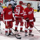 Kris Draper and Henrik Zetterberg stand at center ice during pregame warmups while Jason Williams skates behind them.
