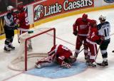 Dominik Hasek curls up in the crease to cover the puck as Nicklas Lidstrom and Henrik Zetterberg hold back LA's Anze Kopitar at the edge of the crease.  Danny Markov has words with former Red Wing Sean Avery behind the goal.