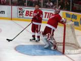 Kris Draper stands at the side of the crease during pregame warmups, next to a stretching Dominik Hasek.