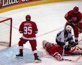 Dominik Hasek sprawls out outside of the crease as Los Angeles King Sean Avery lands on top of him.  Brett Lebda watches Avery while Danny Markov chases after the puck as it goes wide of the net.