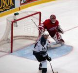 Dominik Hasek watches the puck, looking around Los Angeles King Alexander Frolov stationed at the edge of the crease.