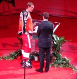 Nicklas Lidstrom, wearing Steve Yzerman's Campbell Conference All-Star jersey, presents Yzerman with a gift from the current Detroit players during the ceremony for Yzerman's number retirement.