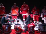 Steve Yzerman walks down a red carpet lined by Red Wings players wearing four of Yzerman's old jerseys at the ceremony for his number retirement.